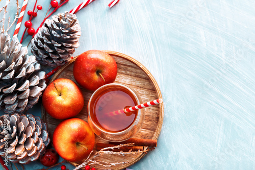 Poster Thee Seasonal and holidays concept. Winter hot tea in a glass with apples and spices on a wooden background. Selective focus, top view