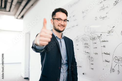 Young dark-haired man in glasses is standing near whiteboard in office Canvas Print