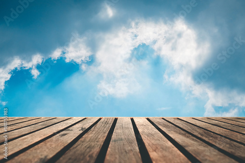 Top of dark brown wooden panel table with light from blue cloudy sky