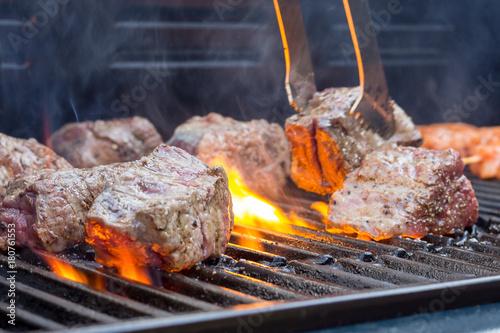 Deurstickers Grill / Barbecue Feuerrote Flamen züngeln um das Grillfleisch auf einem Grillrost, closeup
