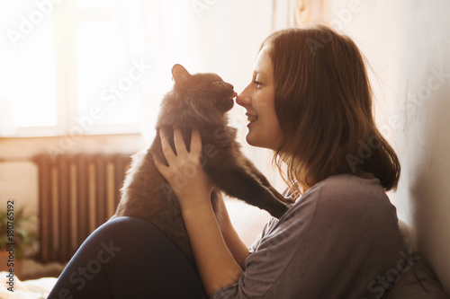 Young woman playing with cat in home. - 180765192