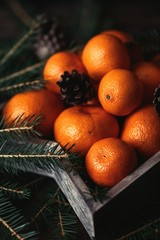 Tangerines with christmas decoration on rustic wooden background. Tangerines with spruce. Christmas decoration