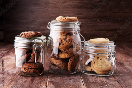 Photo Chocolate cookies in a glass jar on white background.