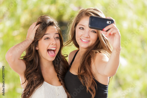 Fotografie, Obraz  Two Attractive Mixed Race Girlfriends Using Their Smart Cell Phones For Selfie O