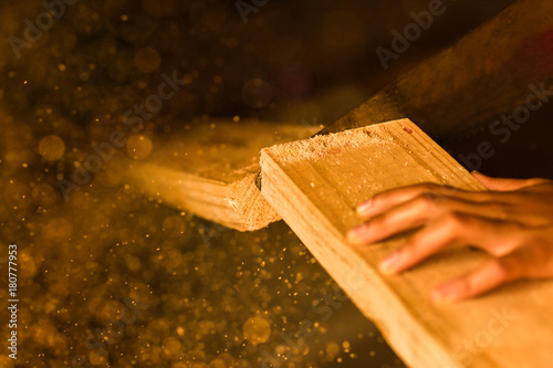 Fotografie, Obraz Woodworking with a handsaw and sawdust in the air