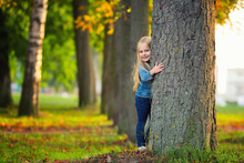 Little Girl Hugging A Tree And...