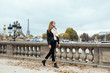Beautiful Parisian girl walking near the Eiffel tower. Woman walking on Paris street