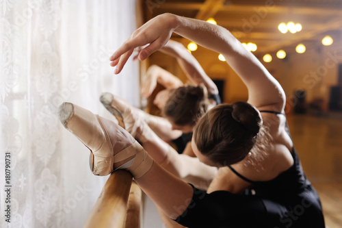 three young cute ballerinas perform exercises on a choreographic machine or barr Canvas Print
