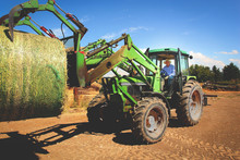 Elderly Farmer Working On Farm With Tractor