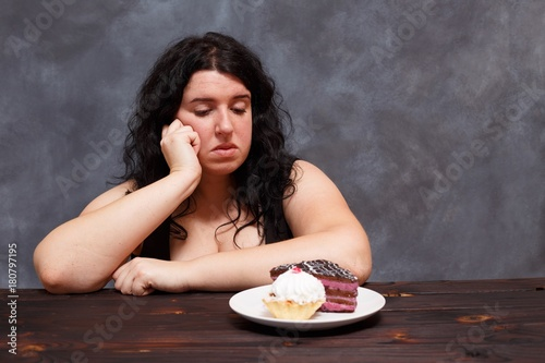 Fotografía  Young upset overweight woman bored of diets looking on sweets, copy space