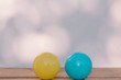 Yellow surprise face ball and sad crying blue ball on wooden table and bokeh wall with copy space