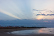 The first rays of the sun appear from behind the clouds, in the distance people walking on the beach at dawn