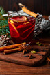 Christmas mulled wine with spices in cup on dark background. Hot mulled wine, with lemon, anise, cinnamon, cloves, cardamom. Autumn dark still life. Mulled wine with slice of lemon and spices.