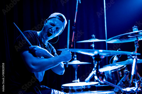 Photo Young drummer posing in front of the camera in a blue concert light