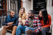canvas print picture - Multiracial group of friends having fun together in London. Two girls and two boys, talking and laughing. Residential district with houses and cars on background. Lifestyle and friendship concepts.