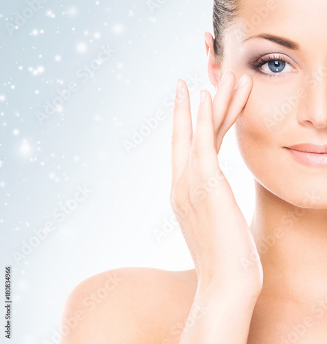 Foto op Aluminium Spa Face of attractive and healthy woman over seasonal Christmas background with a winter snowflakes. Healthcare, spa, makeup and face lifting concept.