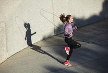 Healthy Woman Skipping Ropes O...