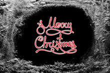 Merry Christmas Text On Black Background And Hoarfrost Snow Frost On Xmas Window