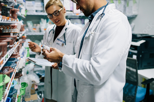 Photo sur Toile Pharmacie Pharmacists checking inventory at pharmacy
