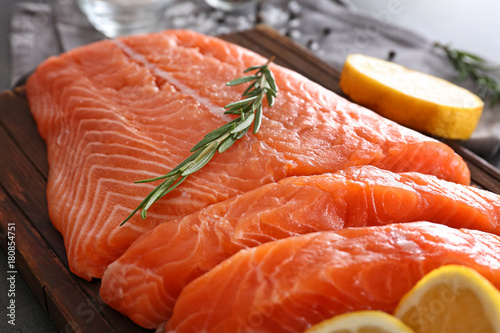 Fresh raw salmon fillet and rosemary on board, closeup