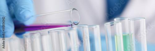 Fotografia  A male chemist holds test tube of glass