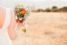 The Bride Is Holding Wedding Bouquet From Orange, Whire, Pink Flowers And Standing On Background Of The Autumn Nature After Wedding Ceremony. Bride Is Dressed In Cream Lace Dress.