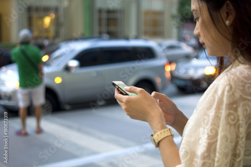 A woman is waiting for a cab using her phone Fototapete