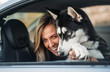 blonde girl with her dog inside the car
