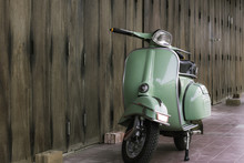 Green Scooter Against Old Hous...