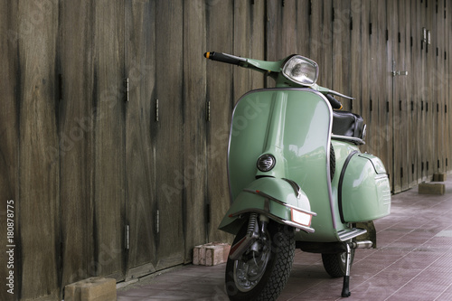 Deurstickers Scooter Green scooter against old house. wood wall mossy surface of building as background. Urban street in Thailand, Asia. Moped parked at moldy wood wall. Asian lifestyle and popular transport.