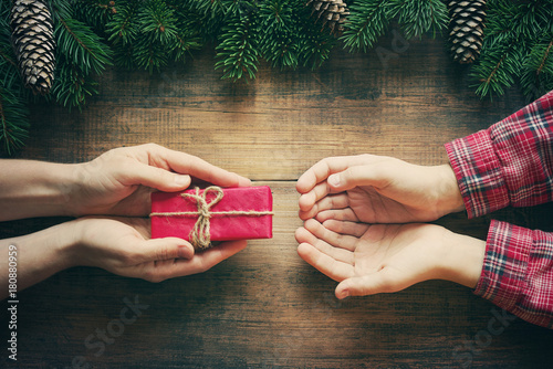 Fotografia  Red gift box in female hands and the child's hands accepting a gift, christmas fir tree on wooden background