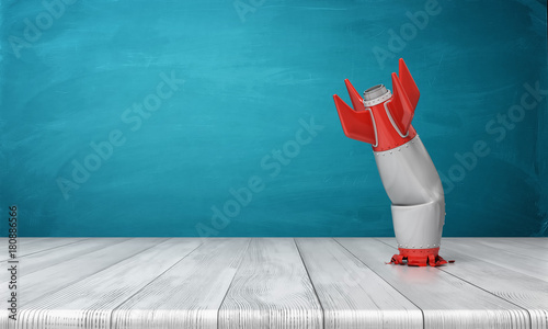 Photo  3d rendering of a red and silver realistic model of a retro rocket stands crashed into a wooden desk on a blue background