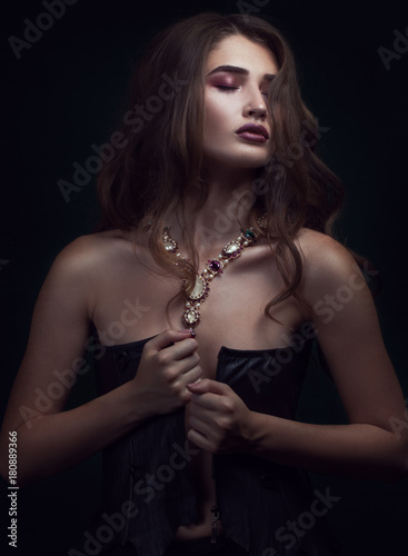 b43ad2abd6a beautiful young woman in sexy black corset. sitting Girl with a necklace on  her neck