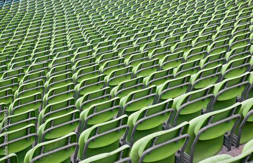 Plakat Rząd rzędy zieleni plastikowi krzesła w stadium, widzieć od behind