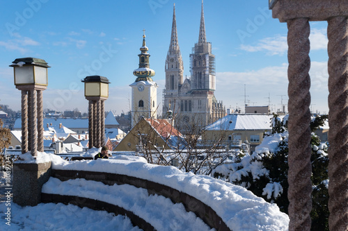 View over Zagreb during winter with snow with view to towers of church and cathedral and seating area with laternsat a sunny day, Zagreb, Croatia, Europe