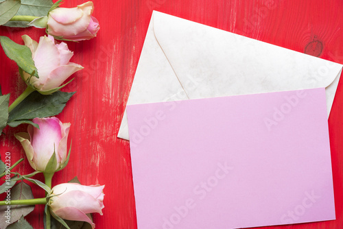 Message card on envelope and roses greeting card idea with a pink message card on envelope and roses greeting card idea with a pink paper on a closed envelope surrounded by roses on a red wooden background m4hsunfo