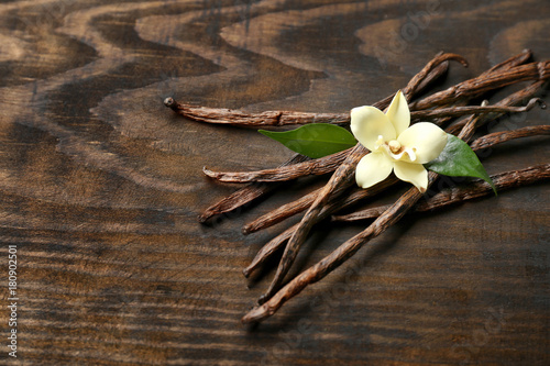 Fotomural  Dried vanilla pods and flower on wooden background