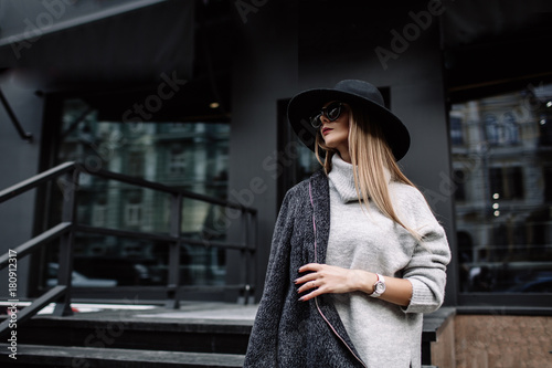 Fototapeta portrait of a young beautiful fashionable woman wearing sunglasses. A model in a stylish wide-brimmed hat. Harmoniously similar clothes in gray tones. Uleach style of shooting. Women's fashion. obraz