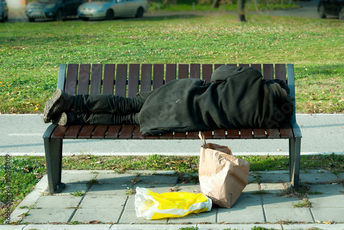 Fotografía  Homeless refugee man in black coat sleeps on the bench on the street
