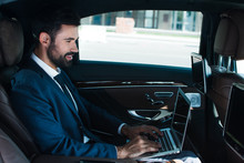 On The Way To Successful Meeting. Side View Of Handsome Young Man Using Laptop With Smile While Sitting In Car
