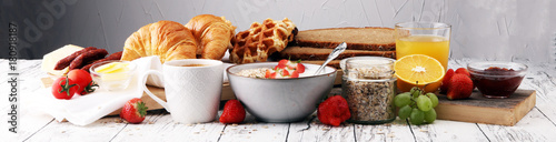Fotografie, Obraz Breakfast served with coffee, orange juice, croissants, cereals and fruits