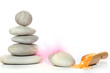 Set for a spa with a pyramid of stones, a spatula with orange salt and a pink feather
