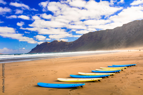 Surfboards on wide sandy beach Famara - famous beach for surfing sport in Lanzarote island