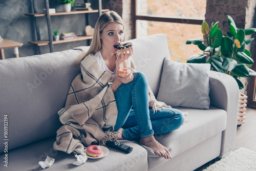 Beautiful blonde woman sitting on couch in living room under blanket eating chokolate donat watching something exciting interesting on television having health problem