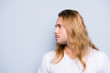 Leinwanddruck Bild - Close up side view photo of  handsome young man with bristle and long blonde hair, isolated on grey background