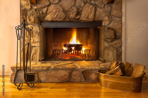 A warm fire in the stone fireplace on a cold night Canvas Print