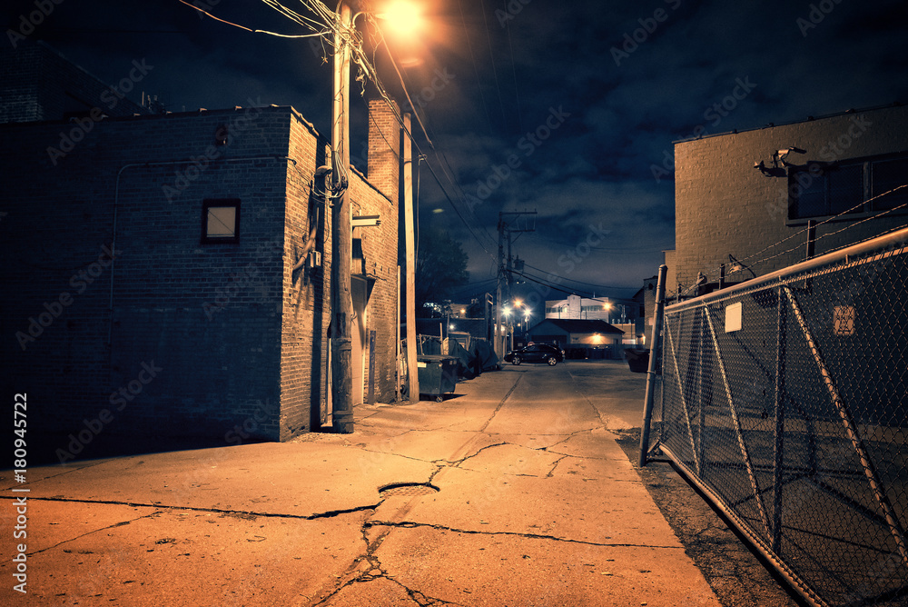 Fototapeta Scary dark city Chicago alley next to an urban warehouse and parking lot.