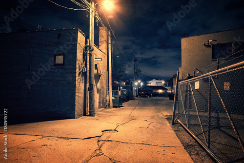 Fototapeta Scary dark city Chicago alley next to an urban warehouse and parking lot. obraz