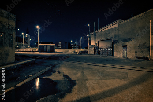 Railroad Dark factory warehouse alley with railroad tracks and rain puddle at night.