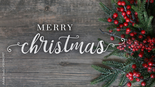 Merry Christmas Text With Evergreen Branches And Berries Over Rustic Dark Wood Horizontal Background